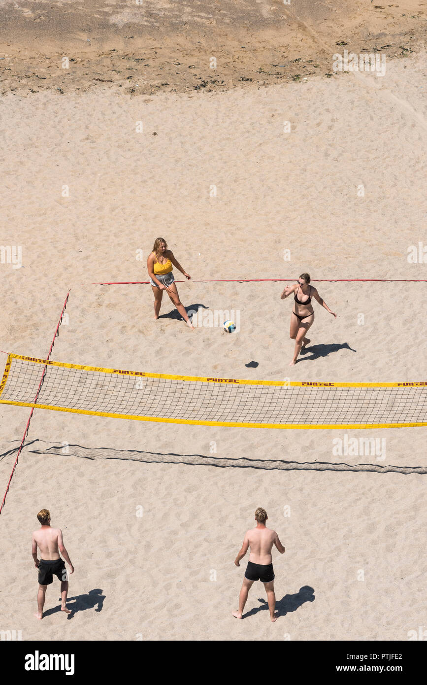 Young people playing beach volleyball on Tolcarne Beach in Newquay in Cornwall. Stock Photo