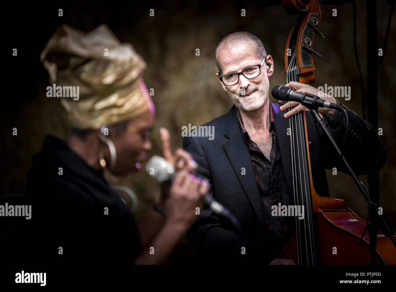 Yan Speake double bassist and Ley Adewole lead vocalist of The Grace Notes performing at Trebah Garden amphitheatre in Cornwall. - Stock Image