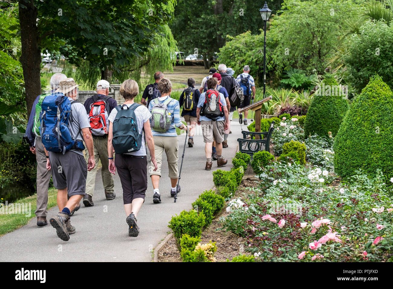 A group of walkers walking through Trenance Park in Newquay in Cornwall. - Stock Image