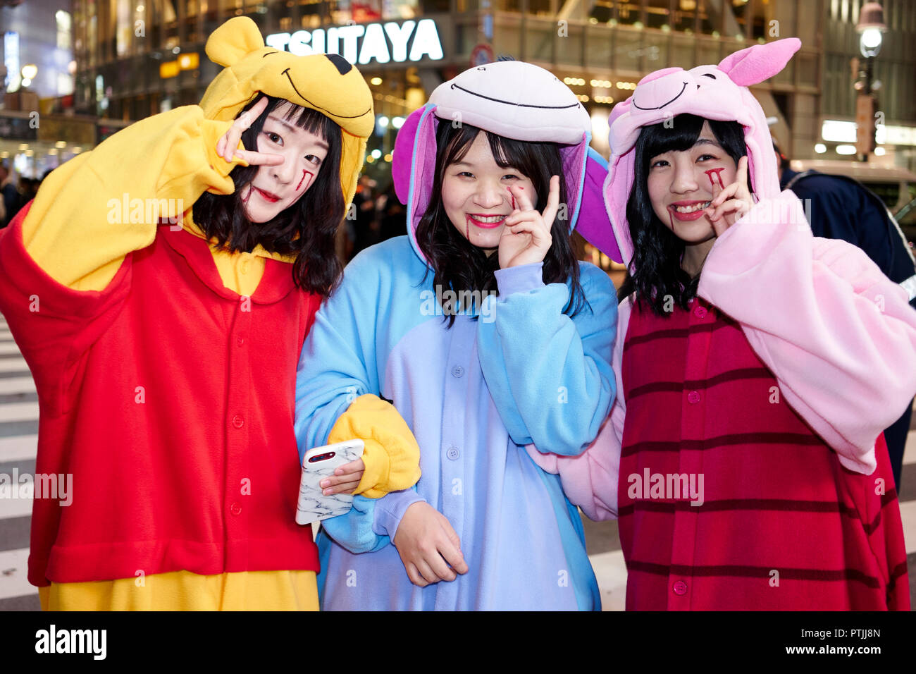 three japanese girls dressed as winnie the pooh with eeyore and