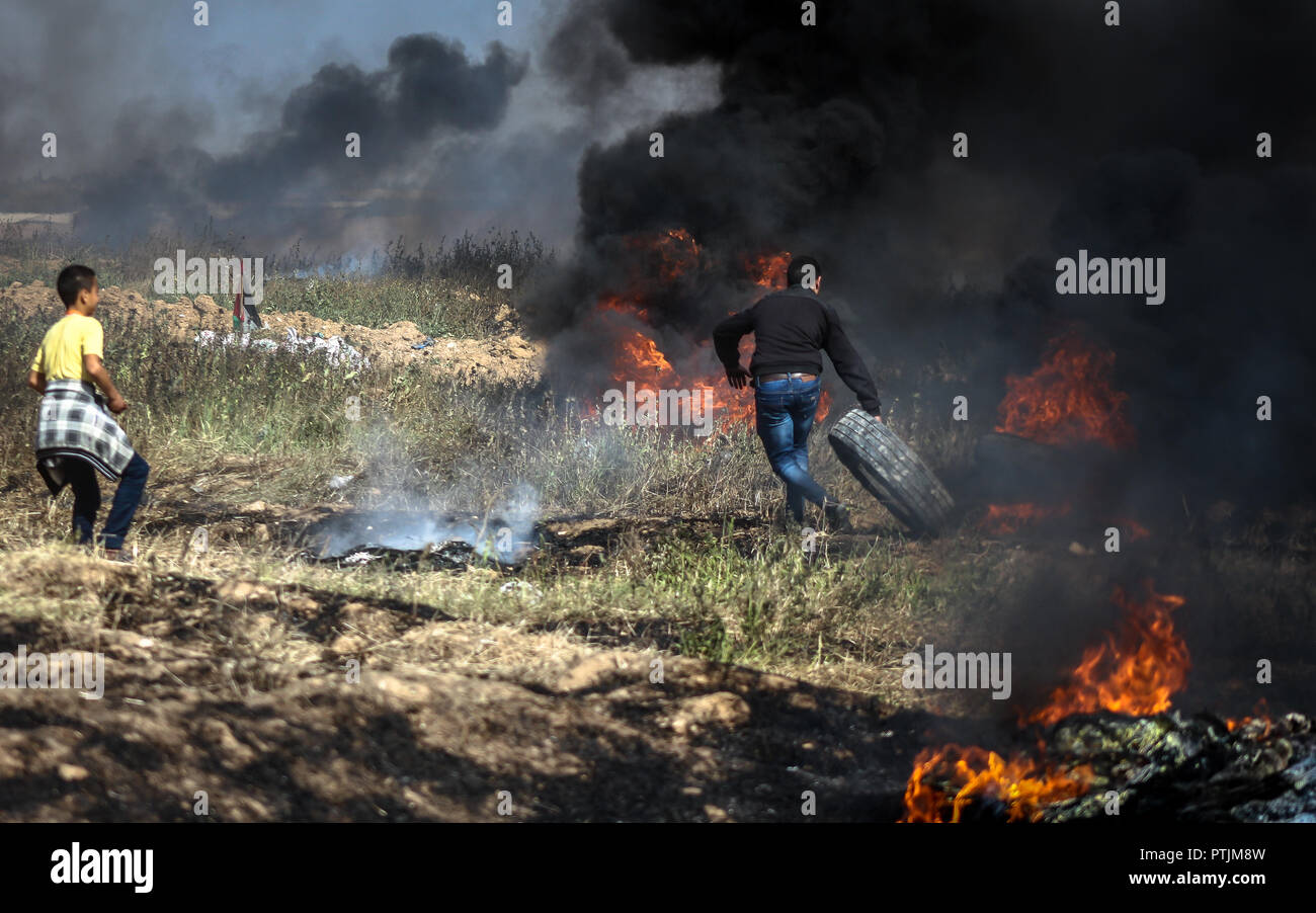 A photo of Palestinian protesters set tires on fire during a demonstration along the border with Israel. - Stock Image