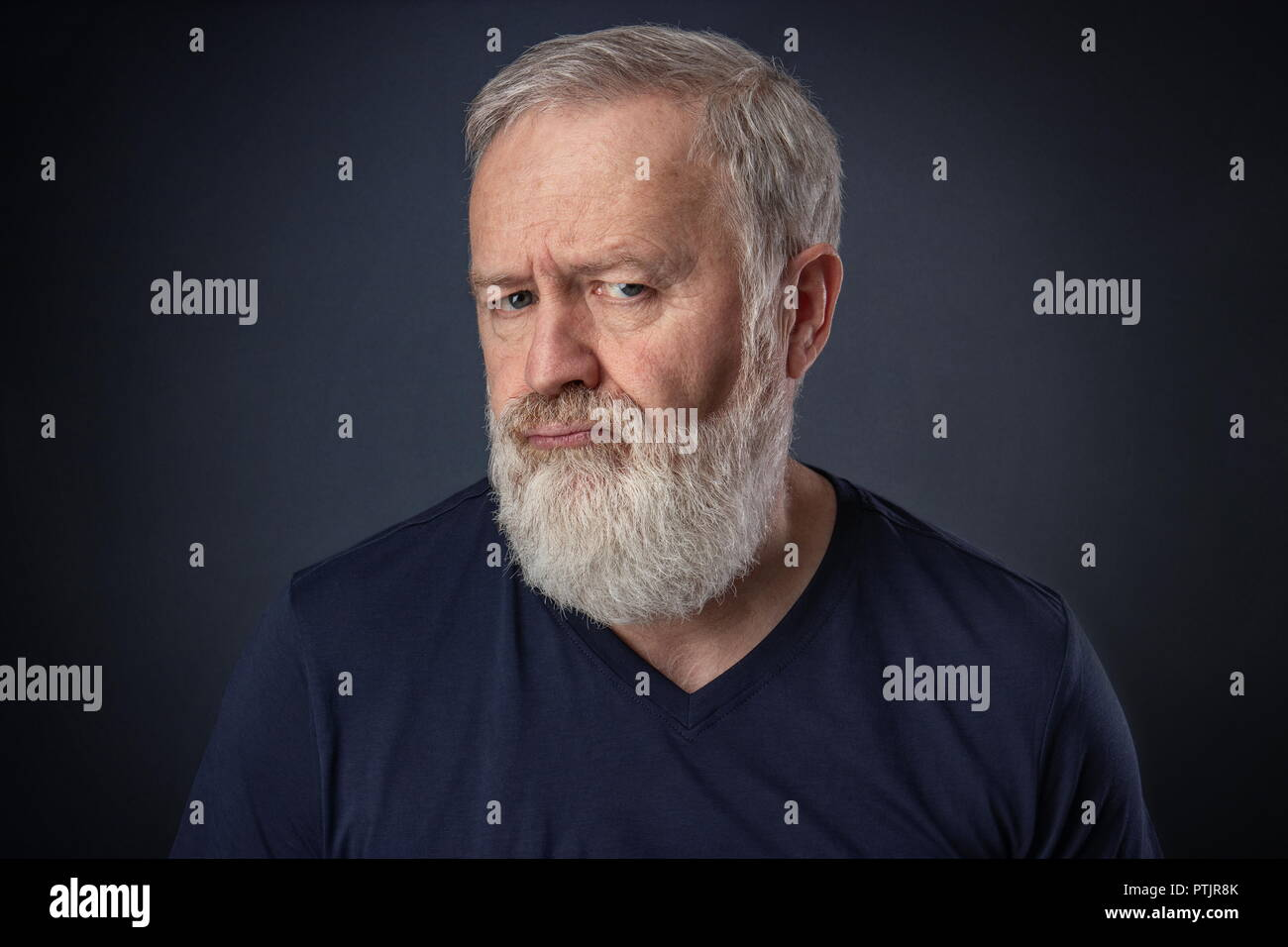 Senior portrait with beard with a mocking and angry mimic - Stock Image