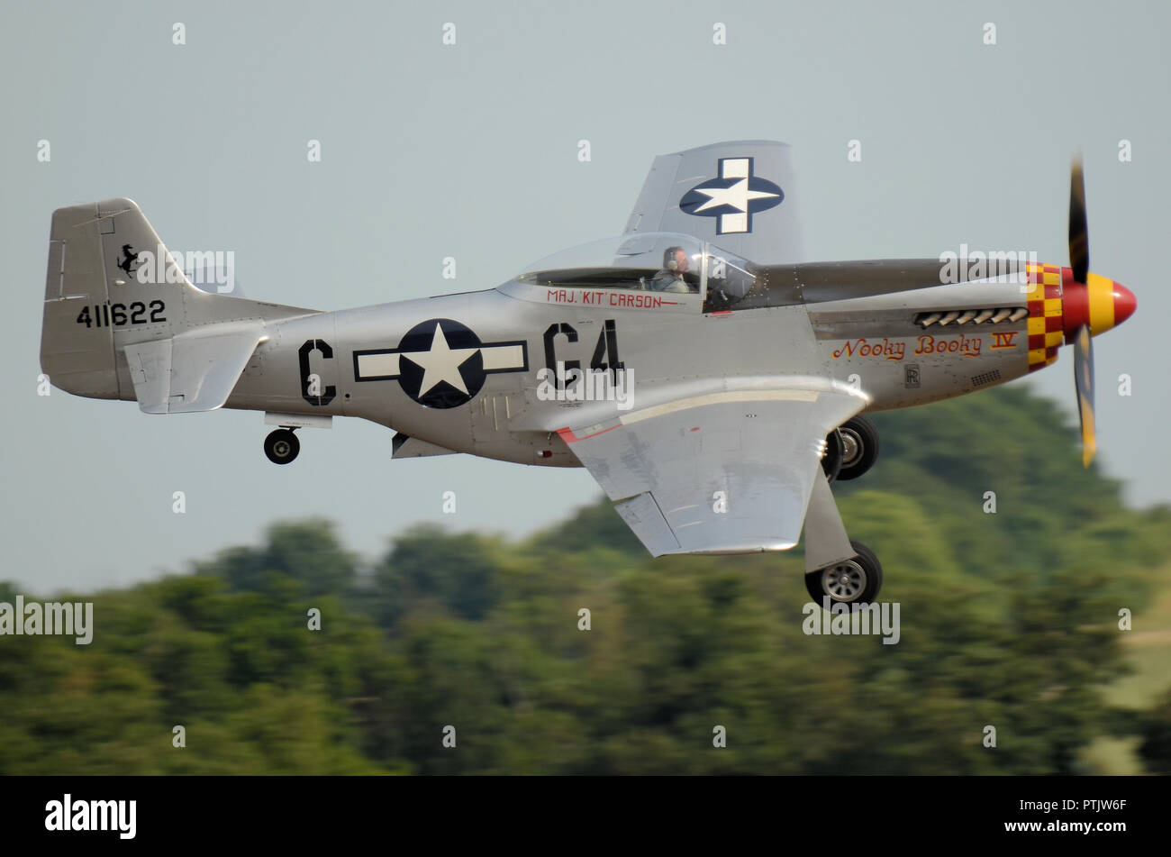 North American P-51 Mustang fighter plane named Nooky Booky IV flying at an airshow. Flying low past trees. Undercarriage down. Space for copy - Stock Image