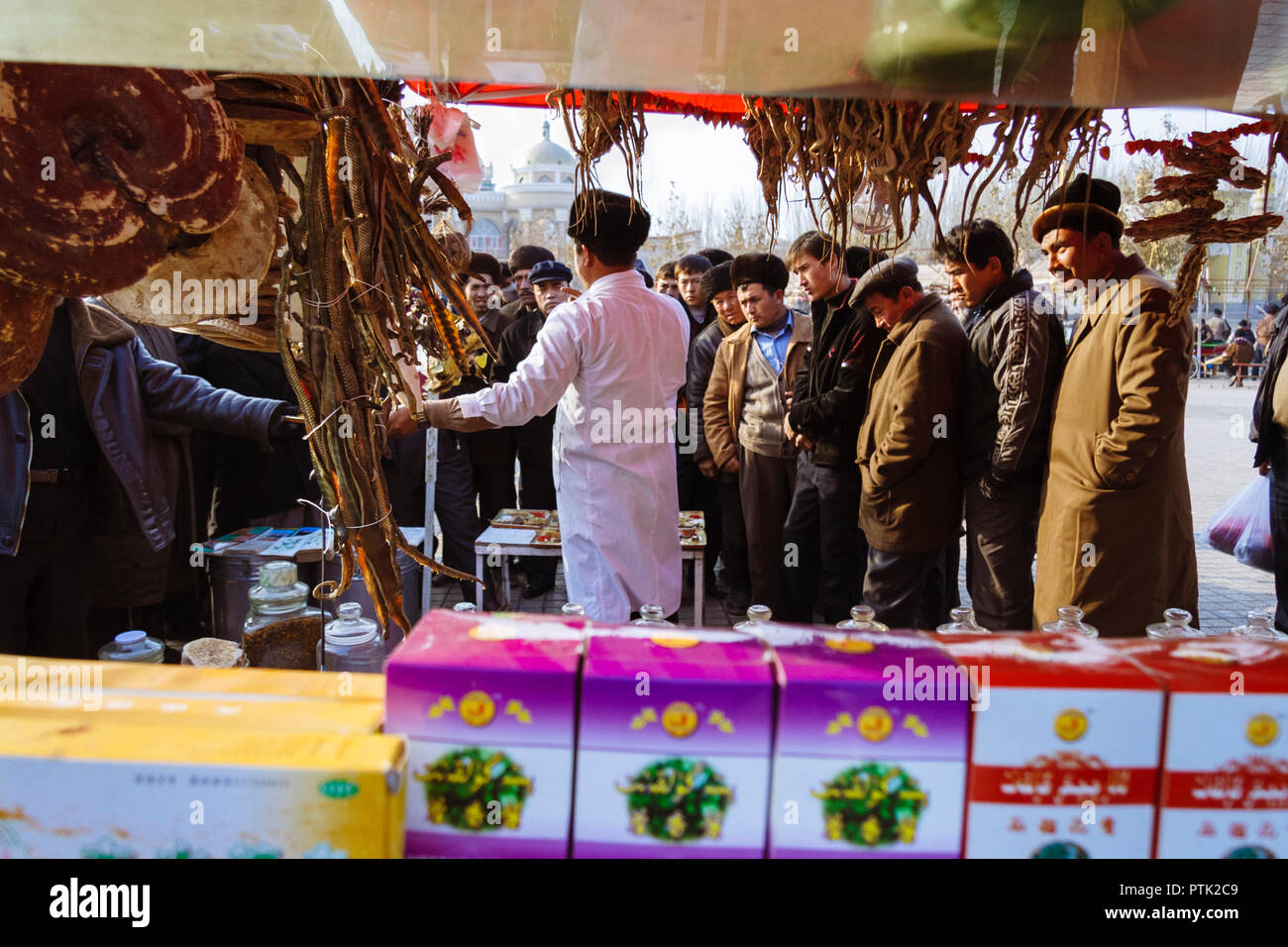 Kashgar, Xinjiang, China : Uyghur men gather around a traditional chemist´s stall at the Sunday Bazaar. - Stock Image