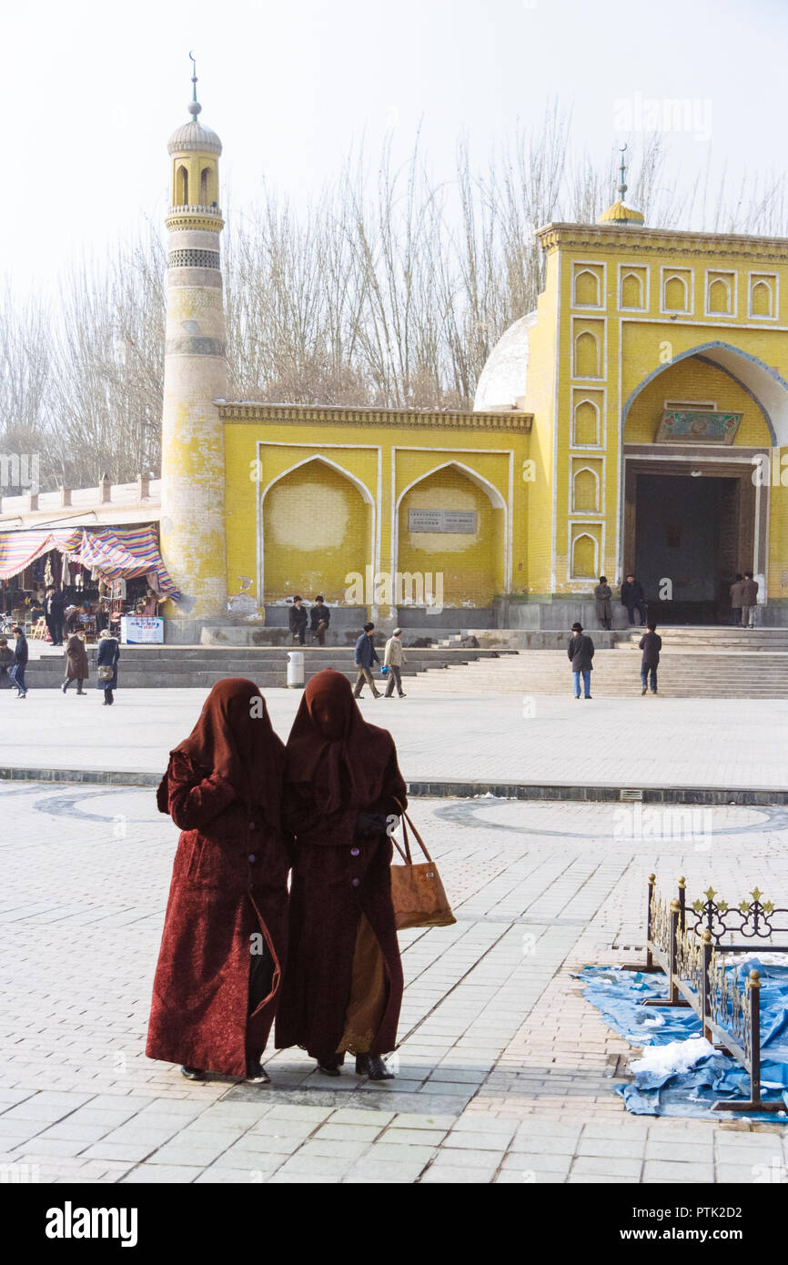 Kashgar, Xinjiang, China : Two Uyghur veiled womenwalk past the yellow-tiled Id Kah Mosque (1442), the spiritual and physical heart of the city. - Stock Image