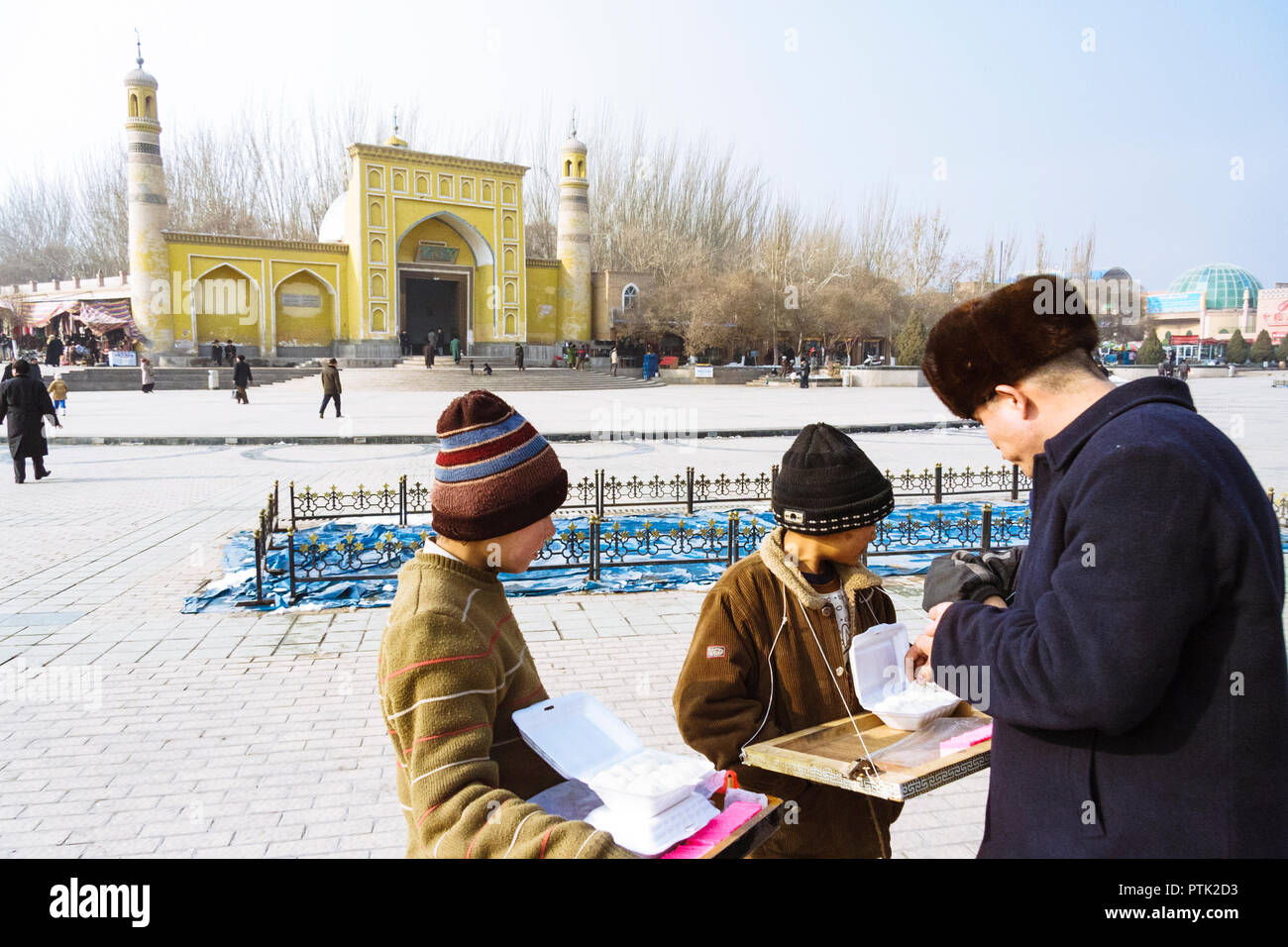 Kashgar, Xinjiang, China : Two Uyghur children sell sweets opposite the yellow-tiled Id Kah Mosque (1442), the spiritual and physical heart of the cit - Stock Image