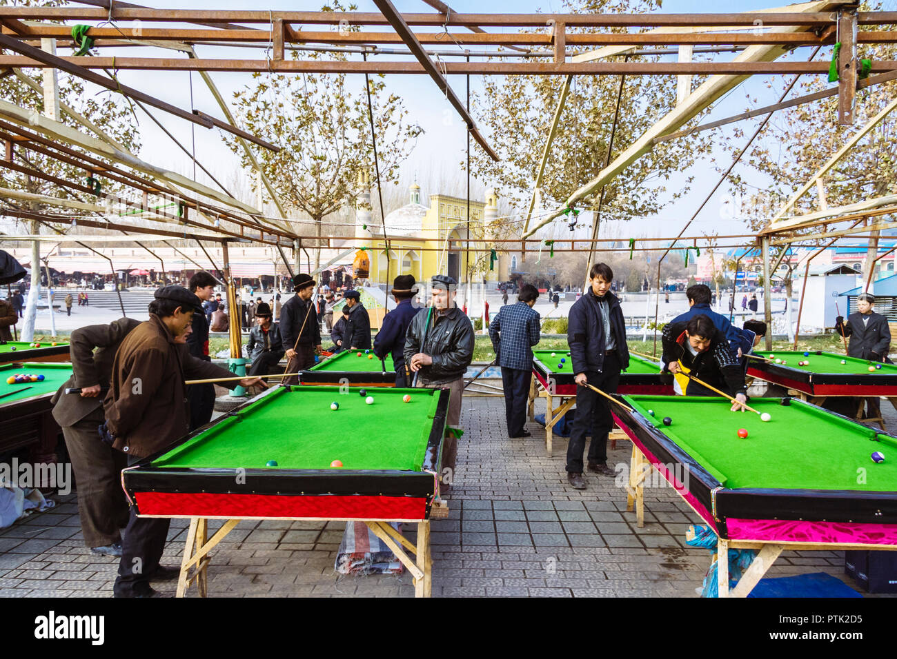 Kashgar, Xinjiang, China : Uyghur men play pool opposite the yellow-tiled Id Kah Mosque (1442) the spiritual and physical heart of the city and the la - Stock Image