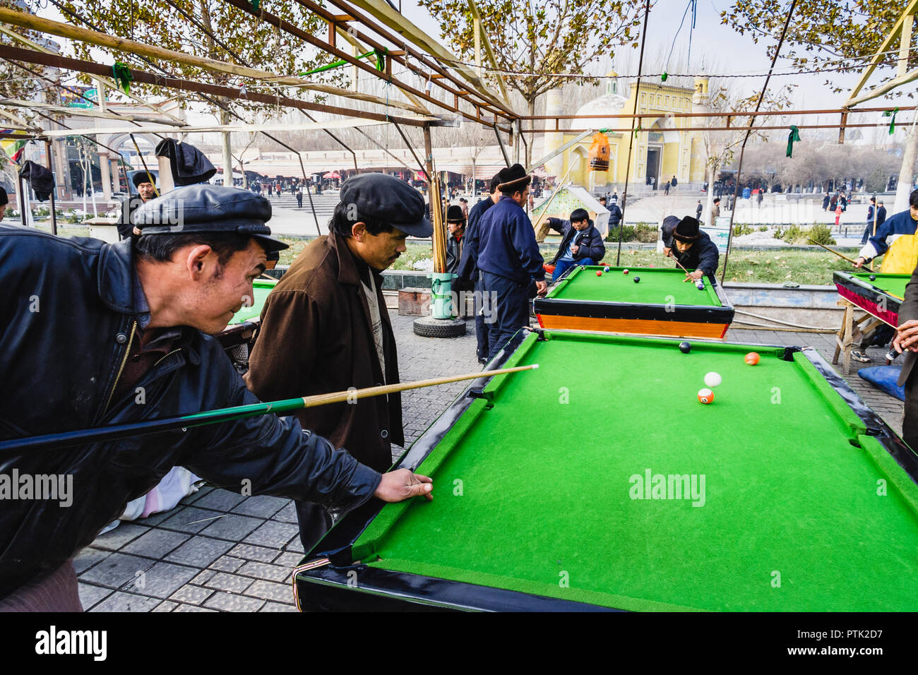 Uyghur men playing pool outside by the Id Kah Mosque. Kashgar, Xinjiang, China - Stock Image