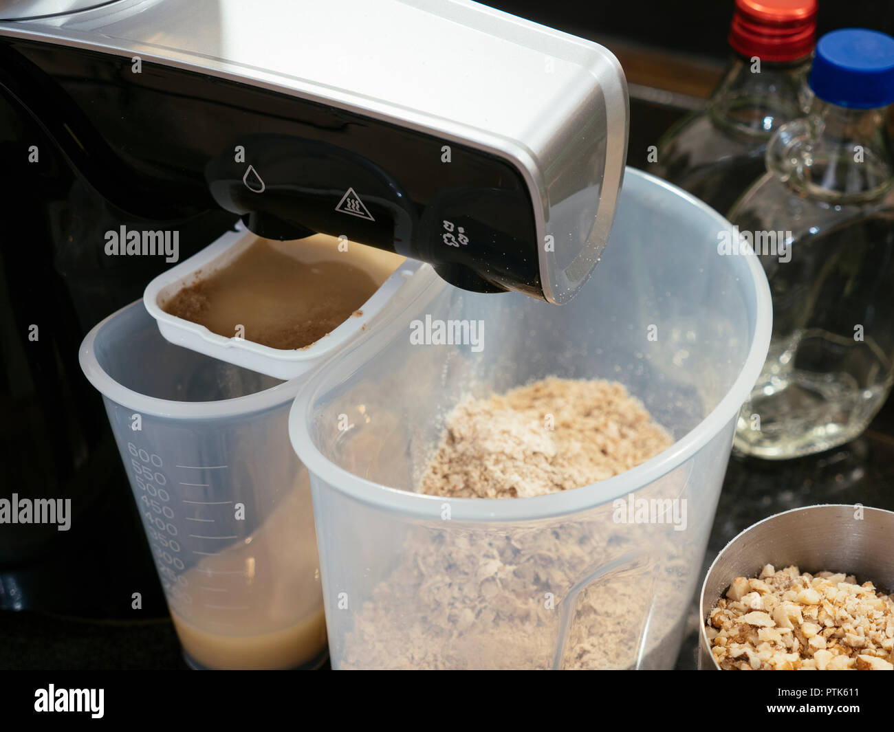 Homemade cold-pressed walnut oil being extracted by an oil press machine. Stock Photo