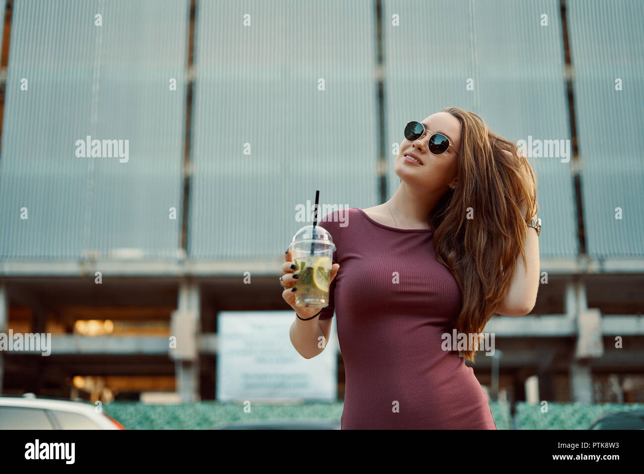 Pensive careless smiling woman in the street drinking refreshing lemonade. City morning concept. - Stock Image
