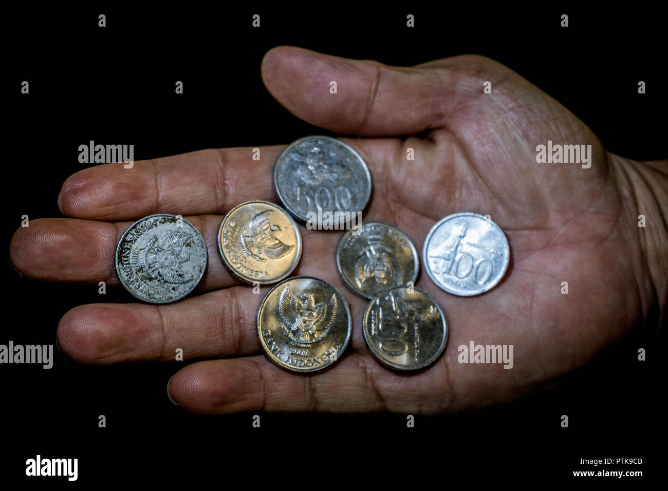 Indonesia rupiah coins in the hand of an asian person isolated. Concept of small salary not enough for the living - Stock Image