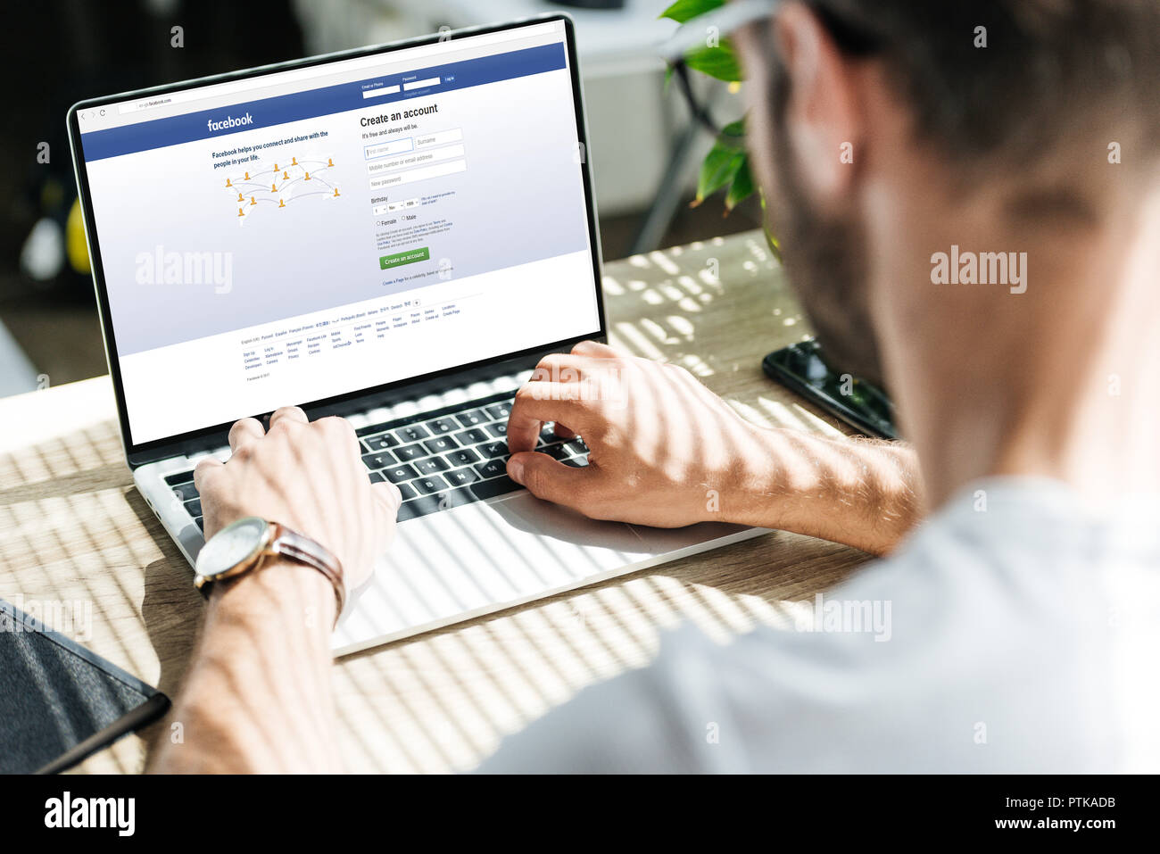 partial view of man using laptop with facebook website on