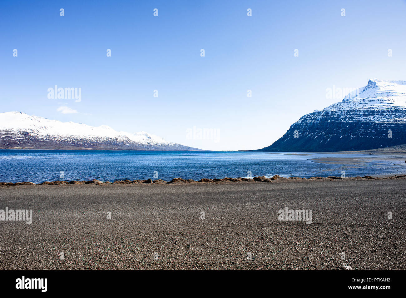 Seydisfjordur, Eastern Fjords, Iceland. Snow capped mountain peaks, sparkling waters and blue sky background - Stock Image