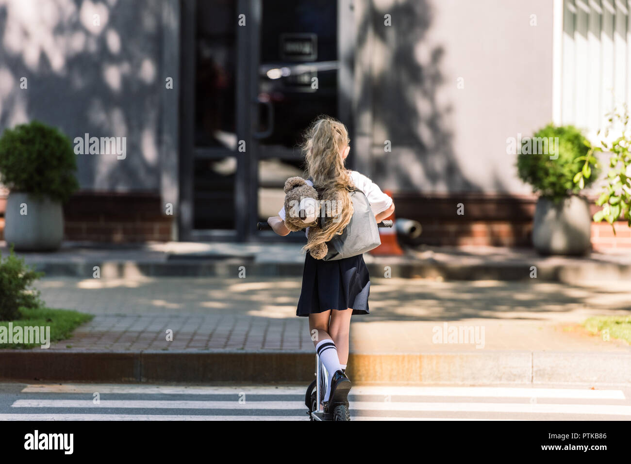 rear view of cute little schoolkid with backpack and teddy bear riding scooter on street - Stock Image