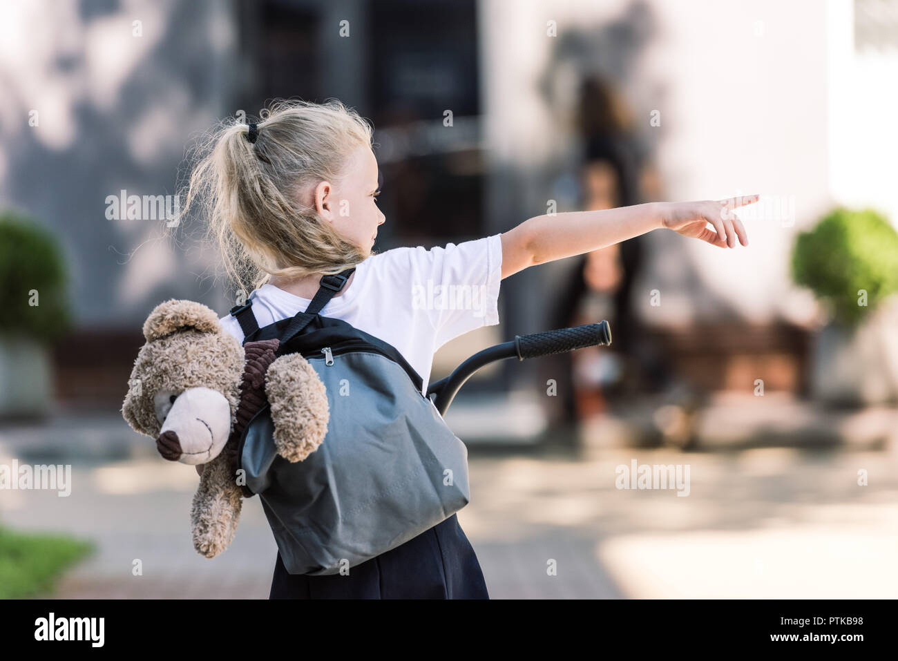 back view of adorable little schoolgirl with backpack and teddy bear riding scooter and pointing away with finger on street - Stock Image
