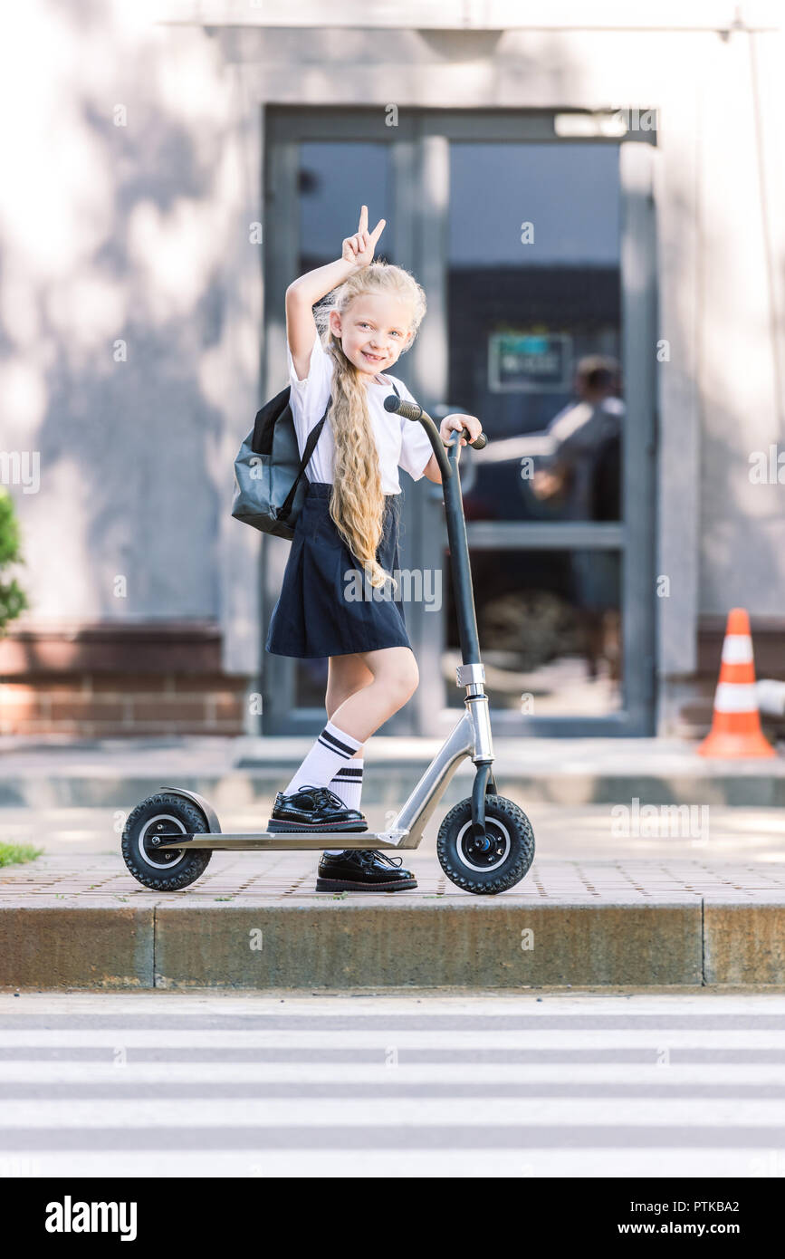 beautiful happy schoolchild with backpack riding scooter and smiling at camera on street - Stock Image
