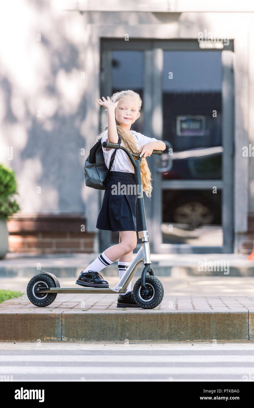 adorable schoolkid with backpack riding scooter, waving hand and looking at camera on street - Stock Image