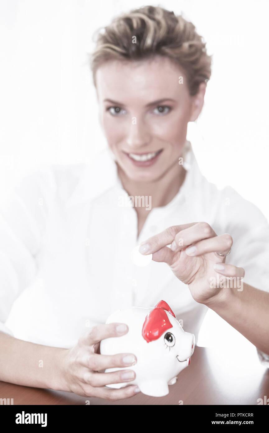 Frau Jung Sparschwein Geld Einwerfen Sparen Muenze Geldstueck Finanzen Ersparnis Sparsamkeit Vermoegensbildung People (Modellfreigabe) - Stock Image