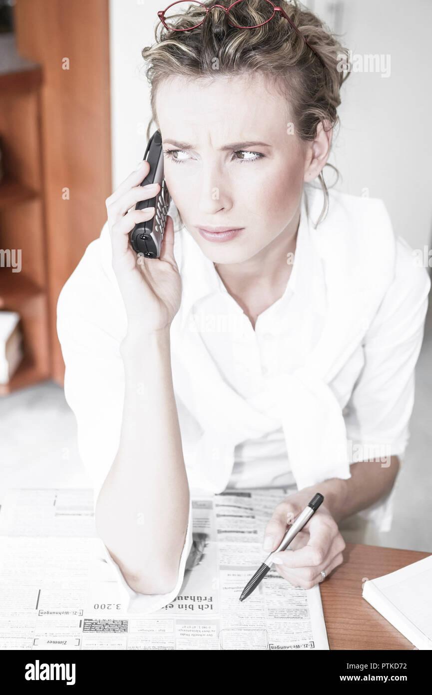 Frau Tageszeitung Stellenanzeigen Markieren Telefonieren Arbeitssuche Arbeitslos Arbeitslosigkeit Jobsuche Zeitung Stellenangebote Stellenmarkt Arbeit Stock Photo