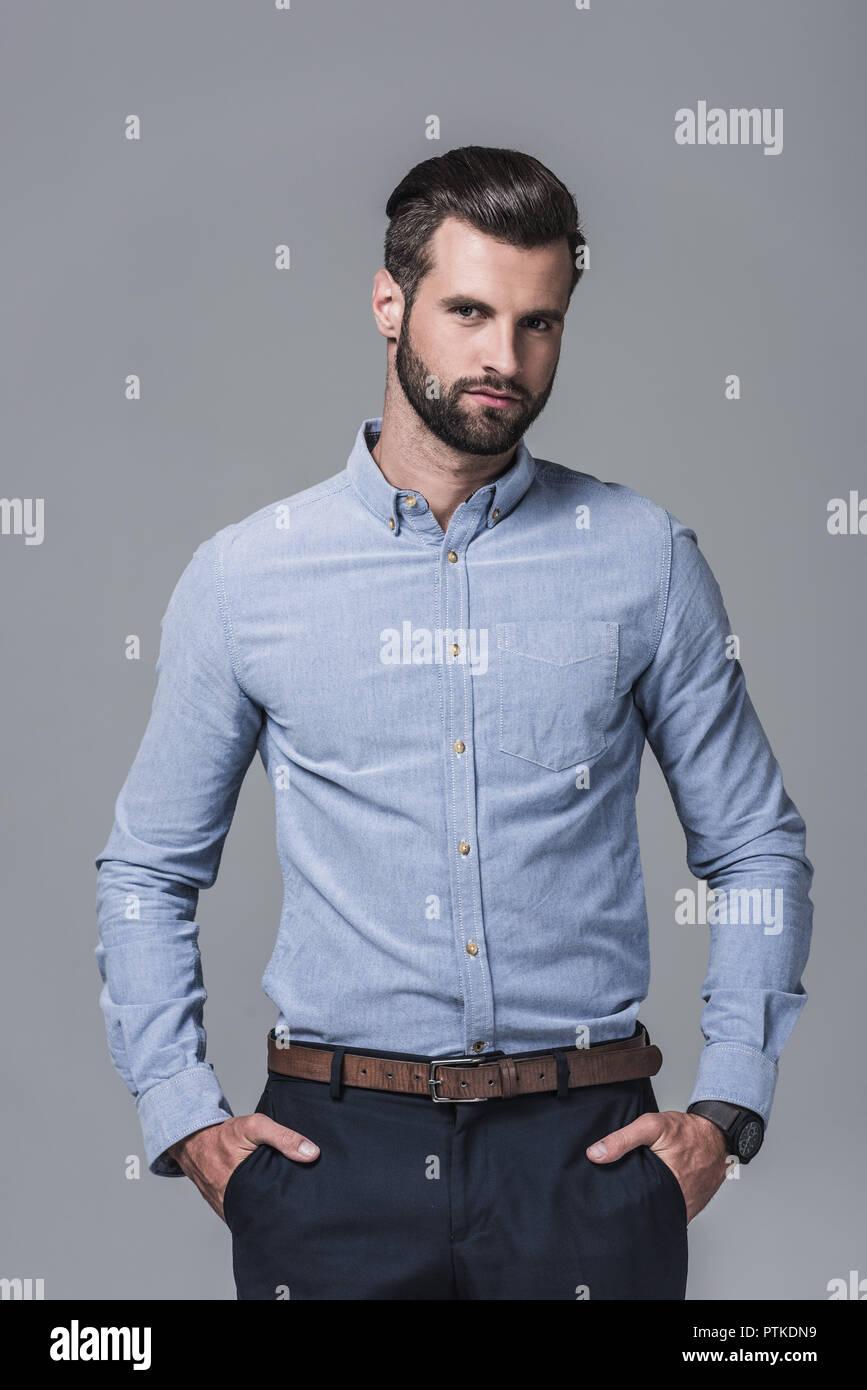 elegant stylish businessman posing in formal wear, isolated on grey - Stock Image