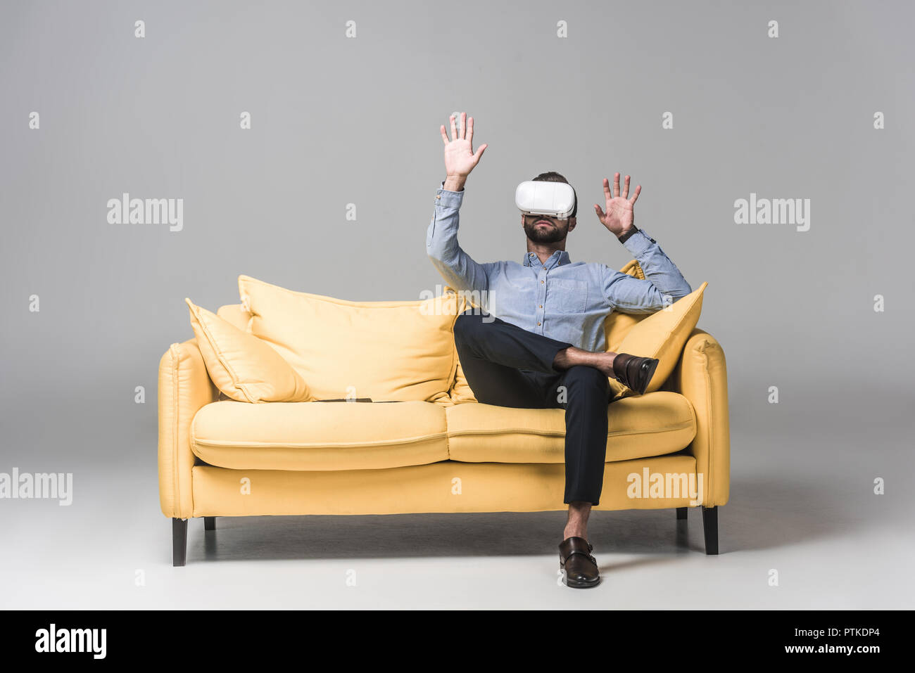 dc760be9e7a bearded man gesturing and using virtual reality headset and sitting on  yellow sofa on grey -