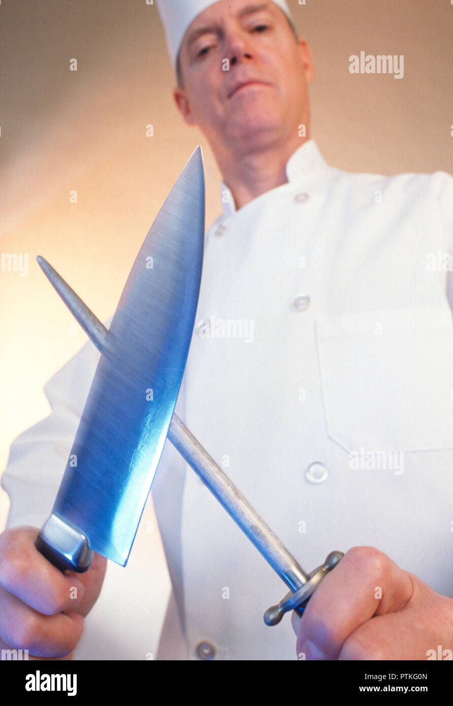 Chef sharpening butcher knife, USA - Stock Image