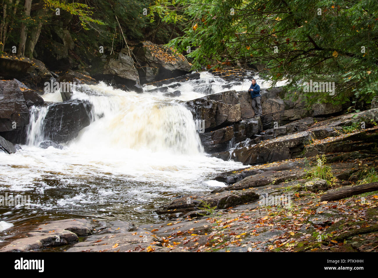 Austin Falls waterfall on the Sacandaga River in the Adirondack Mountains, NY USA with a young man perched on a rock ledge watching the water. - Stock Image