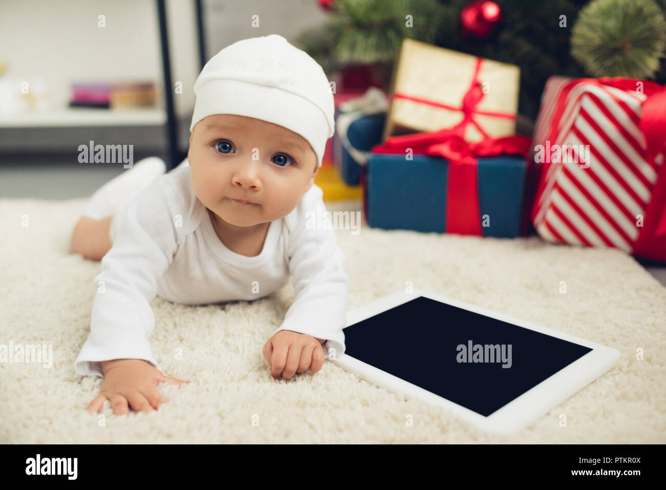 9dd520b019e7 cute little baby with tablet lying on floor with christmas gifts blurred on  background - Stock