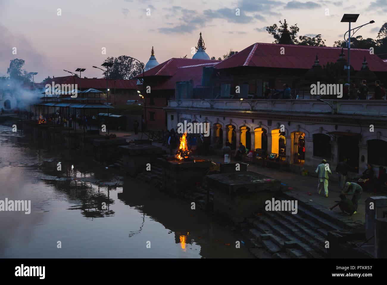 Kathmandu,Nepal - Oct 8,2018:Hindu cremation rituals at the banks of Bagmati river at Pashupatinath Temple premises Aryaghat , Kathmandu. - Stock Image
