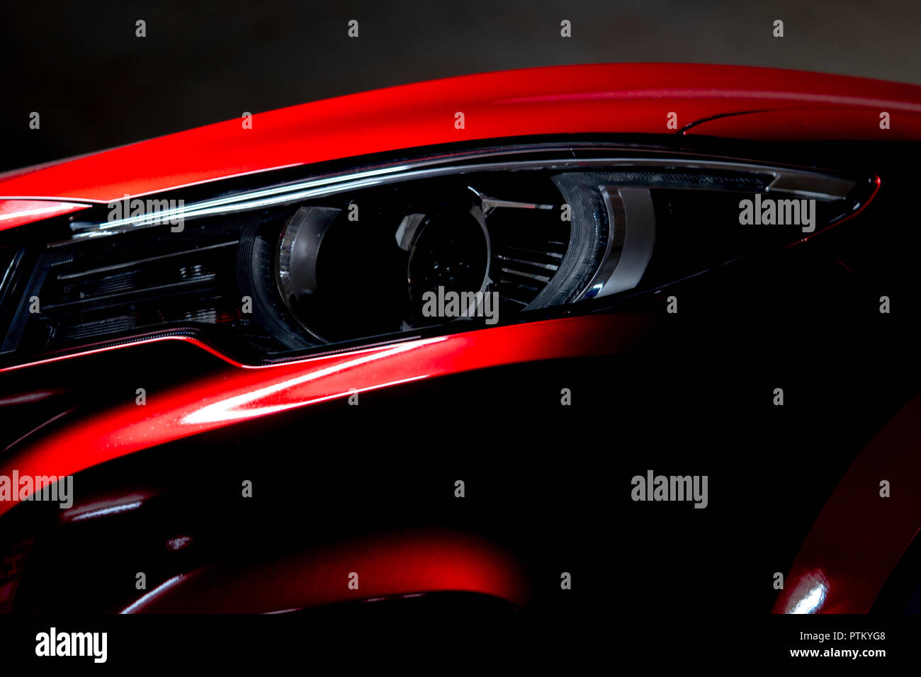 Closeup headlight of shiny red luxury SUV compact car. Elegant electric car technology and business concept. Hybrid auto and automotive concept. Car p - Stock Image