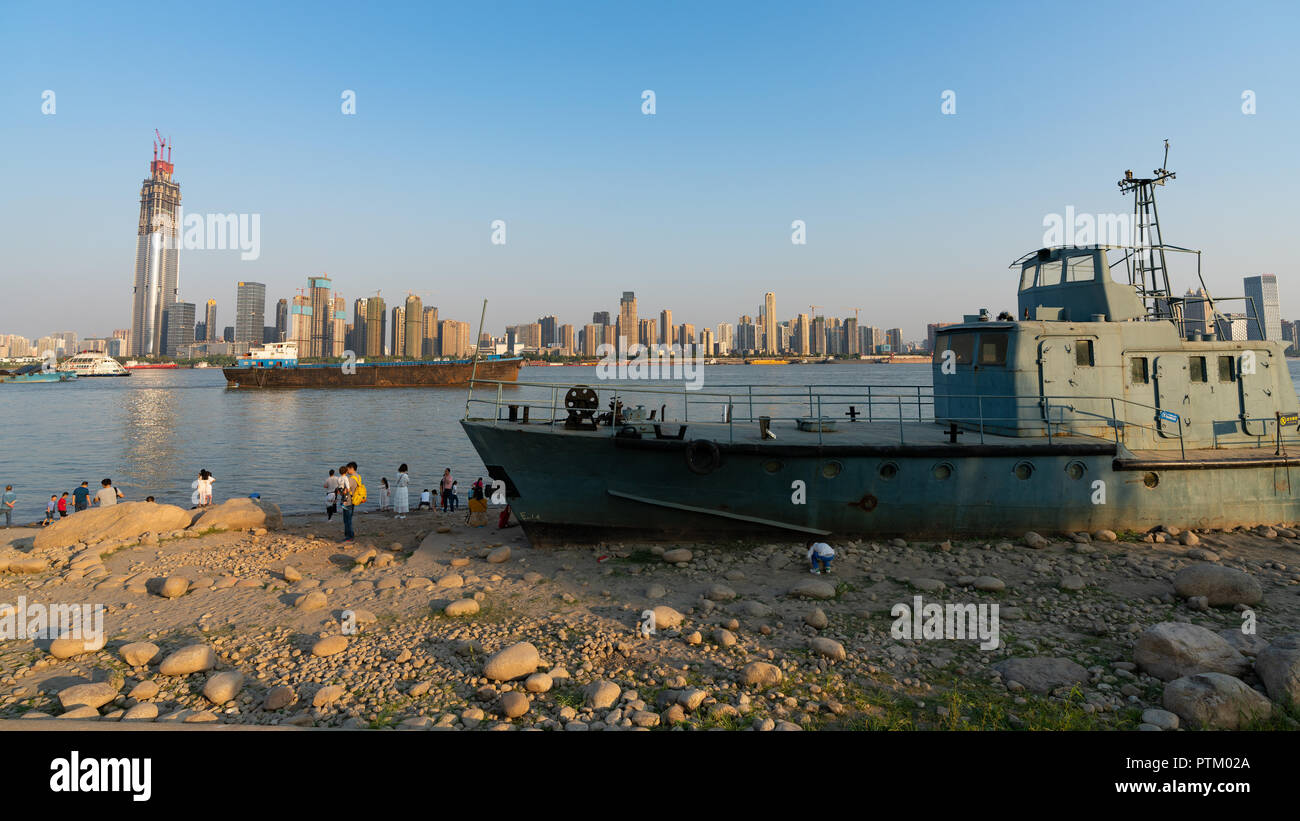 4 October 2018, Wuhan China : Wreck of Chinese naval ship wash ashore on Yangtze riverbank and Wuhan skyline in background in Wuhan Hubei China - Stock Image