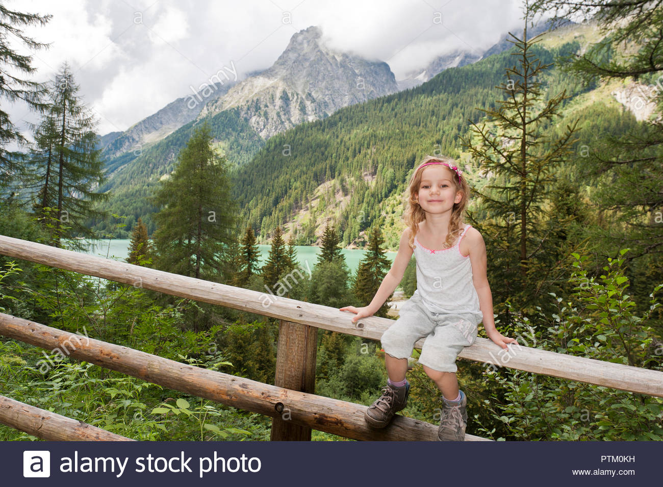Little girl sitting on wooden railings, Lake Antholz in the back, Rasun-Anterselva, Puster Valley, South Tyrol, Italy - Stock Image