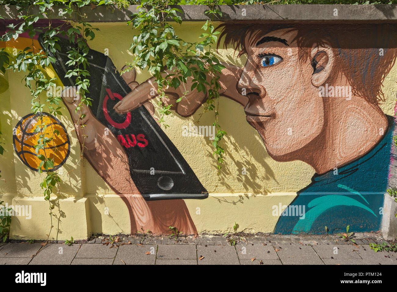 Graffiti on wall, man turns off smartphone, Munich, Upper Bavaria, Bavaria, Germany - Stock Image