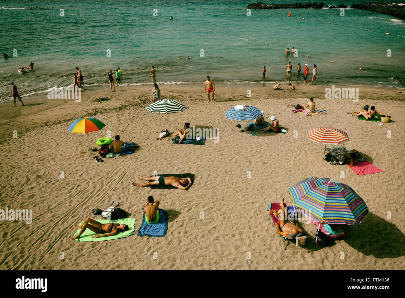 Holidaymakers sunbathe on the beach, Torviscas, Playa El Duque, Costa Adeje, Tenerife, Canary Islands, Spain - Stock Image