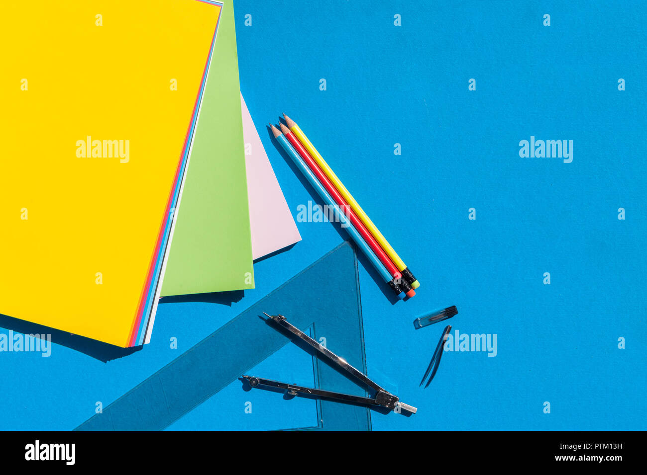 Geometry set with sheets colorful papers, compass, rulers and pencils on blue background - top view - Stock Image