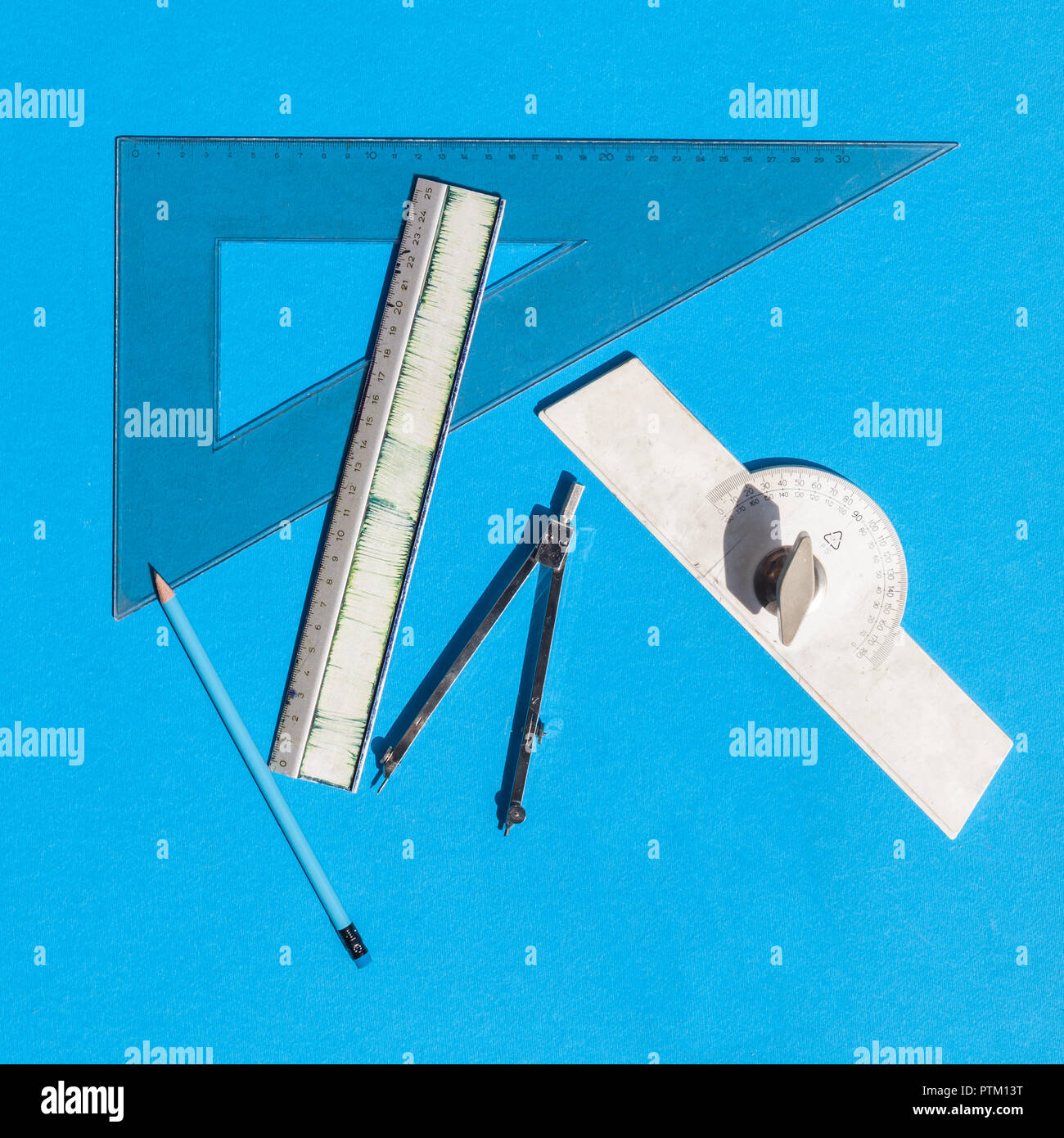 Geometry set with compass, rulers, pencil and protractor on blue background - top view - Stock Image