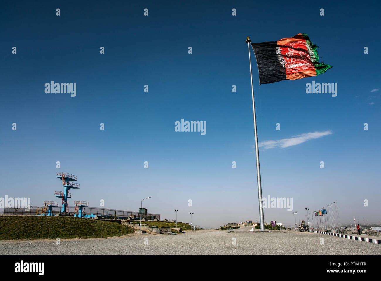 A huge flag of Afghanistan flies at the top of swimming pool hill overlooking Kabul. - Stock Image