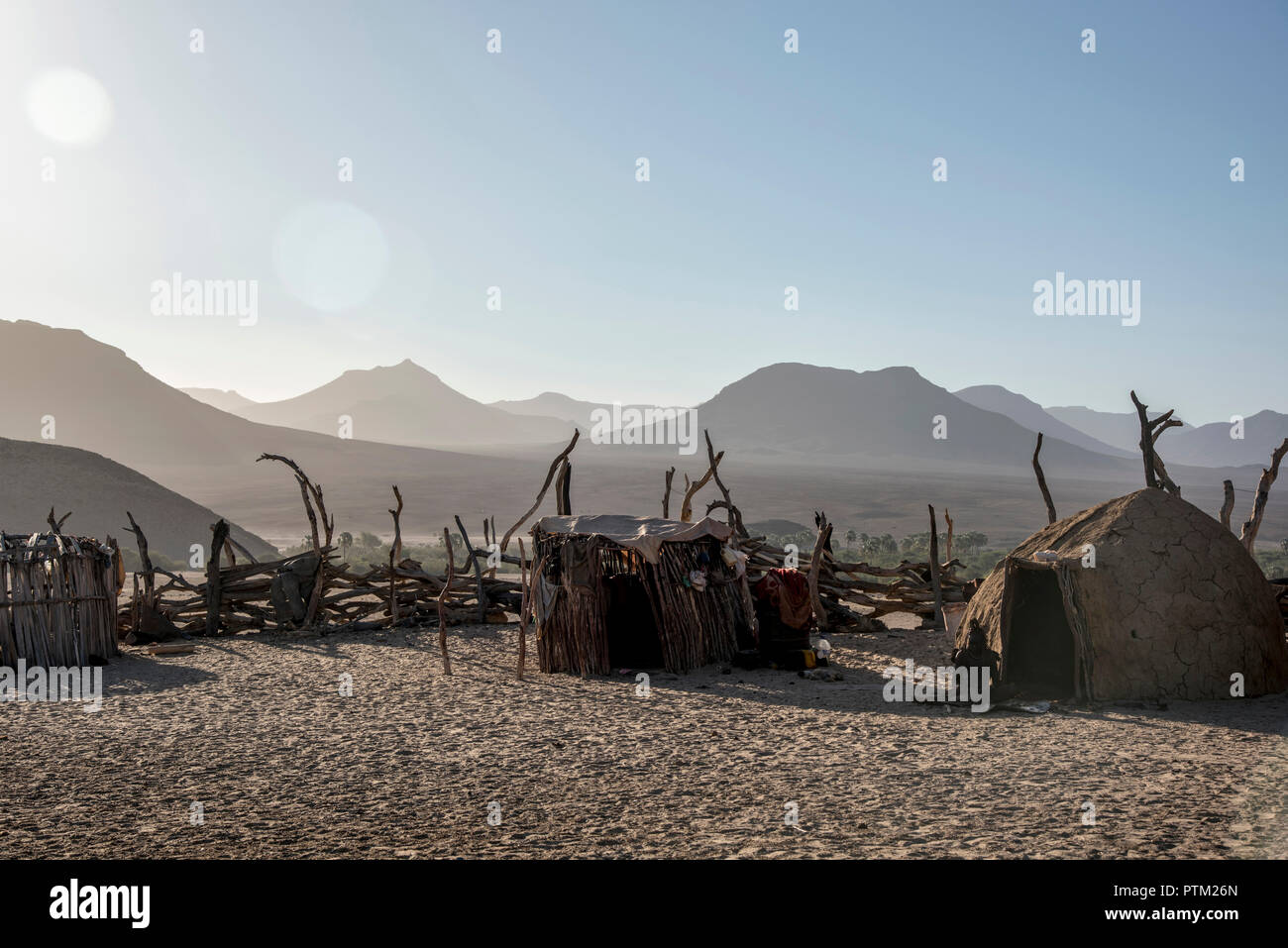 A Himba village with traditional mud huts in the remote province of Kaokaland near to the town of Purros in Namibia. - Stock Image