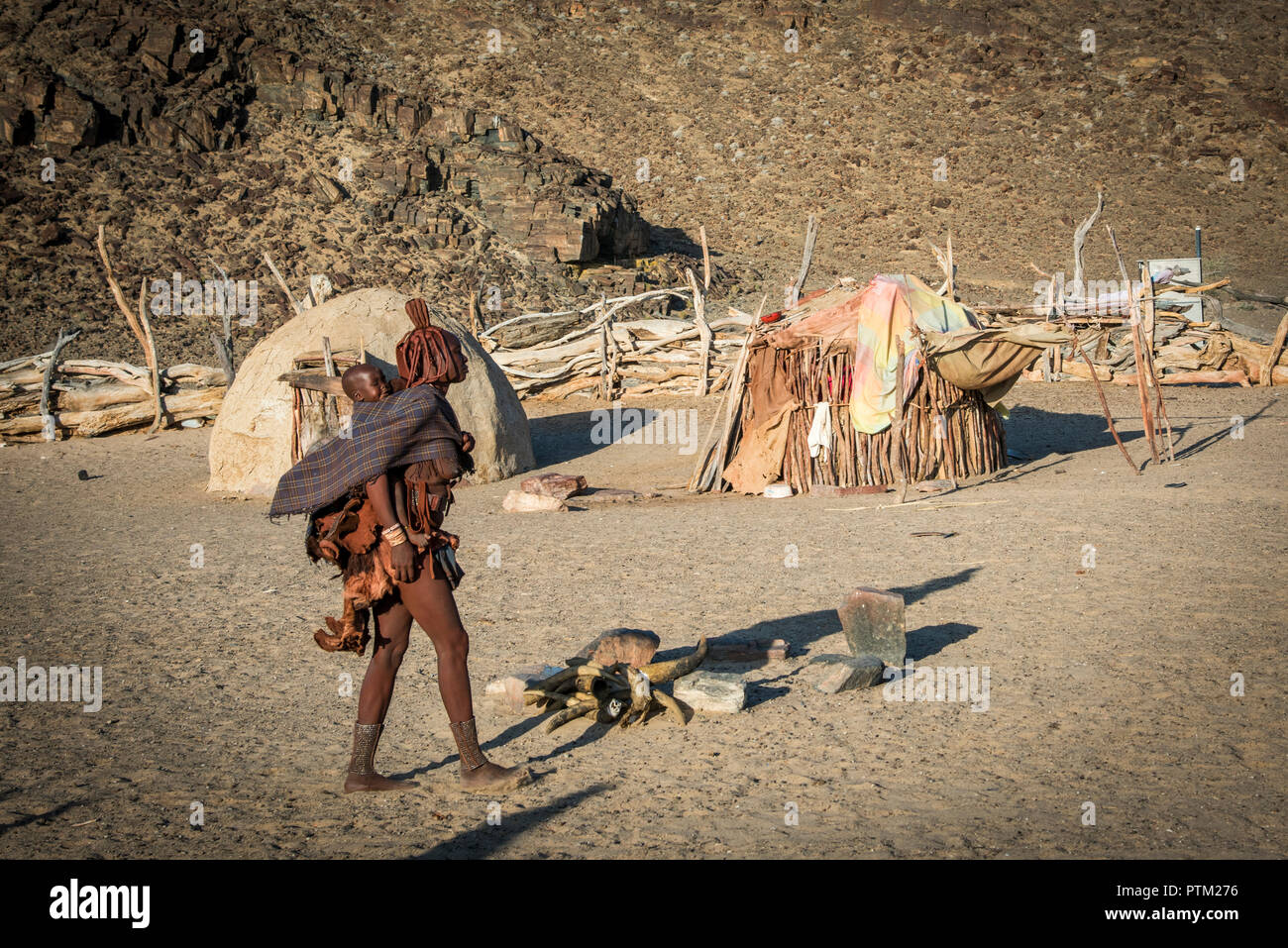 A Himba lady carrying her child walks across her traditional camp situated near to Purros in the remote province of Kaokaland in Namibia. - Stock Image
