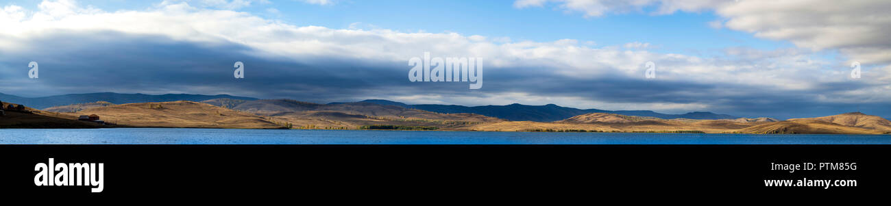 Wide panoramic photo of countryside landscape in autumn day with hill slopes illuminated by sun shining through the cloudy massive sky/ yellow meadows - Stock Image