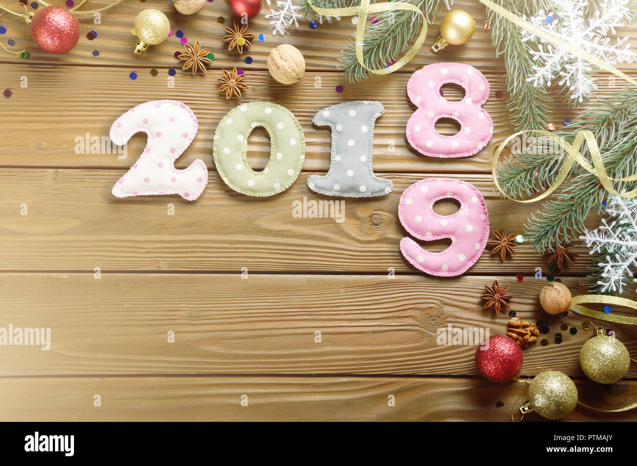 Colorful stitched digits 2 0 1 8 9 of polkadot fabric with Christmas decorations flat lyed on wooden background. Place for text - Stock Image