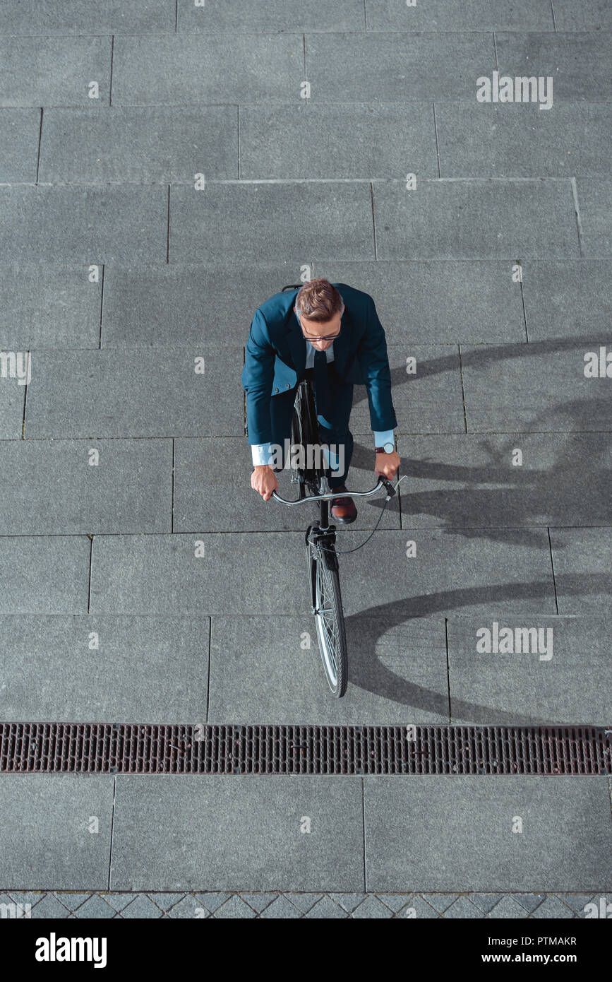 high angle view of businessman in formal wear riding bicycle on street - Stock Image