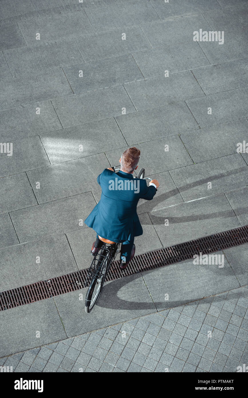 back view of businessman in formal wear riding bicycle on street - Stock Image