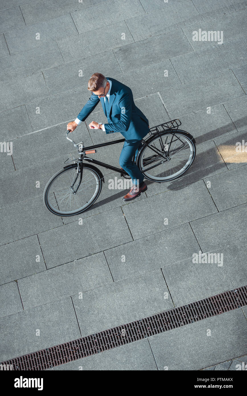 high angle view of businessman in formal wear riding bicycle and checking wristwatch - Stock Image