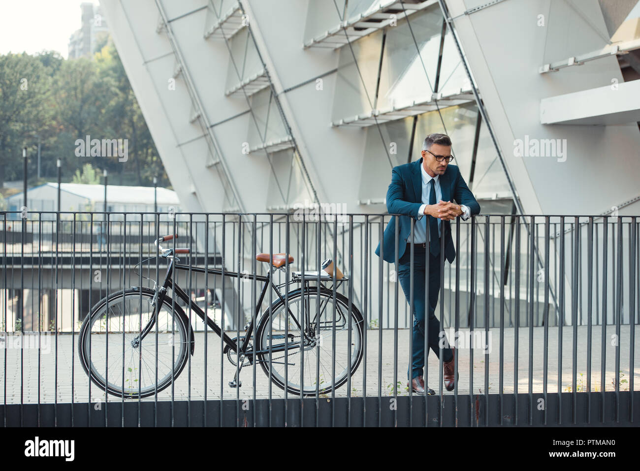 successful middle aged businessman in formal wear leaning at railing near bicycle - Stock Image