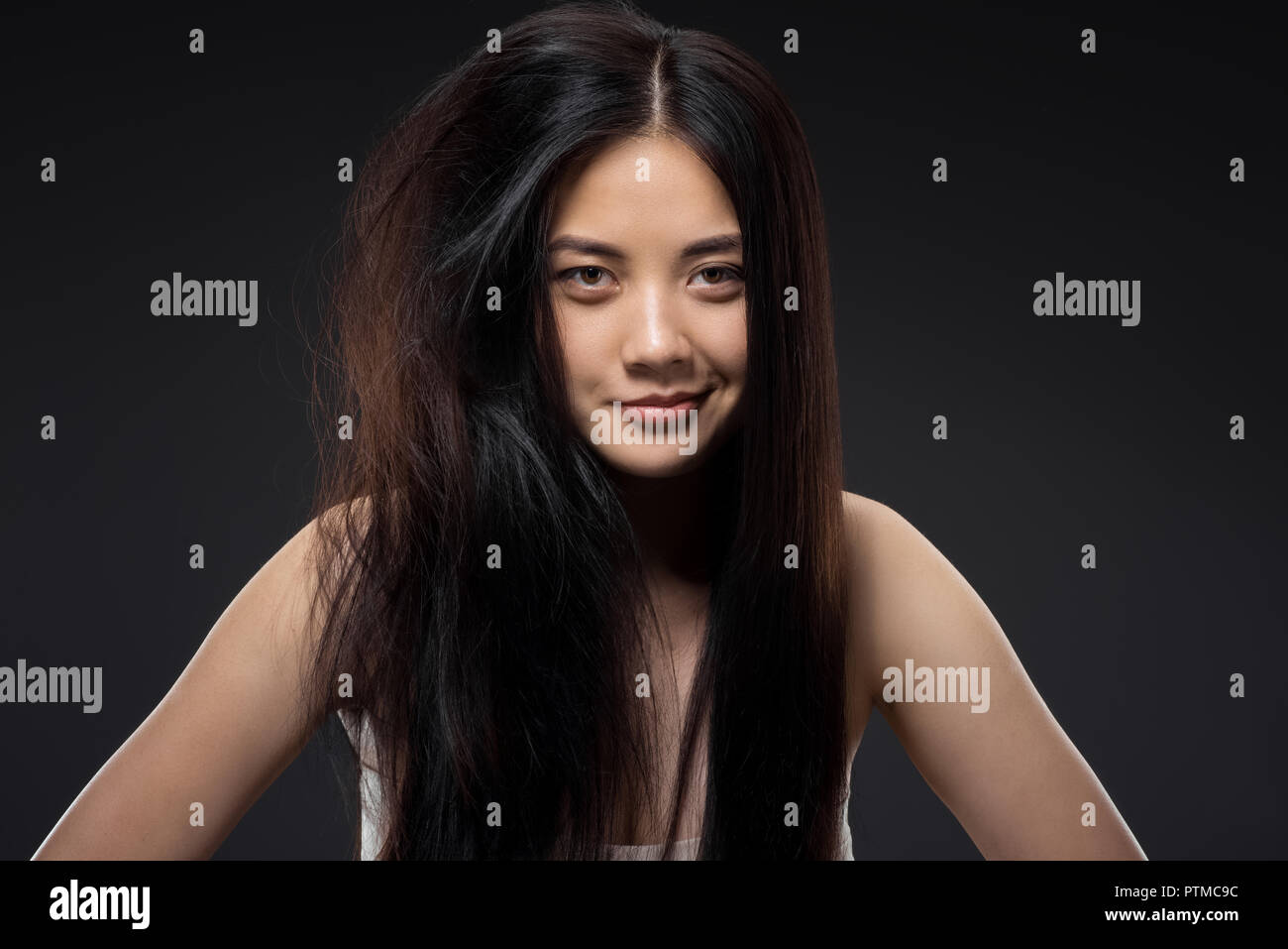 portrait of smiling asian woman with half knotted and straight hair isolated on black, keratin hair treatment concept - Stock Image