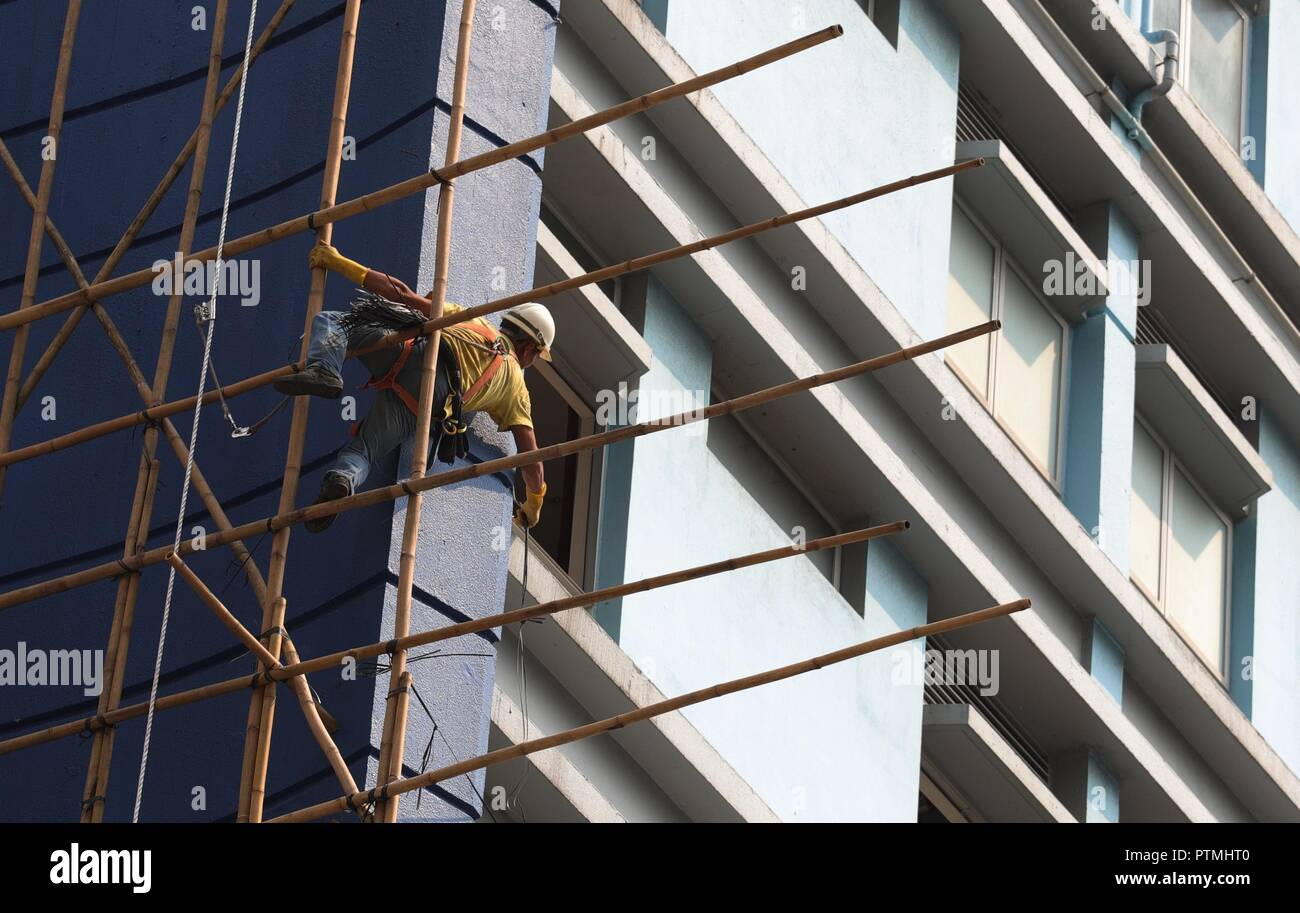 Hong Kong, CHINA. 10th Oct, 2018. A worker perform acrobatic act on the bamboo scaffolding outside the hotel awaiting to be demolished. Hong Kong is a place where Chinese traditional art of bamboo scaffolding is being kept as a classic architectural craft.Oct-10, 2018 Hong Kong.ZUMA/Liau Chung-ren Credit: Liau Chung-ren/ZUMA Wire/Alamy Live News - Stock Image