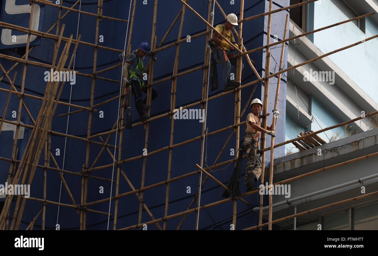 Hong Kong, CHINA. 10th Oct, 2018. Although aluminum pipe scaffoldings are gradually replacing the old art of bamboo scaffoldings, Hong Kong still persist on using traditional Chinese art of bamboo scaffoldings as a classic architectural craft. It is believed that bamboo, with its tenacity and strength, provide better safety and durability as compare to aluminum pipes as a material for scaffoldings.Oct-10, 2018 Hong Kong.ZUMA/Liau Chung-ren Credit: Liau Chung-ren/ZUMA Wire/Alamy Live News - Stock Image