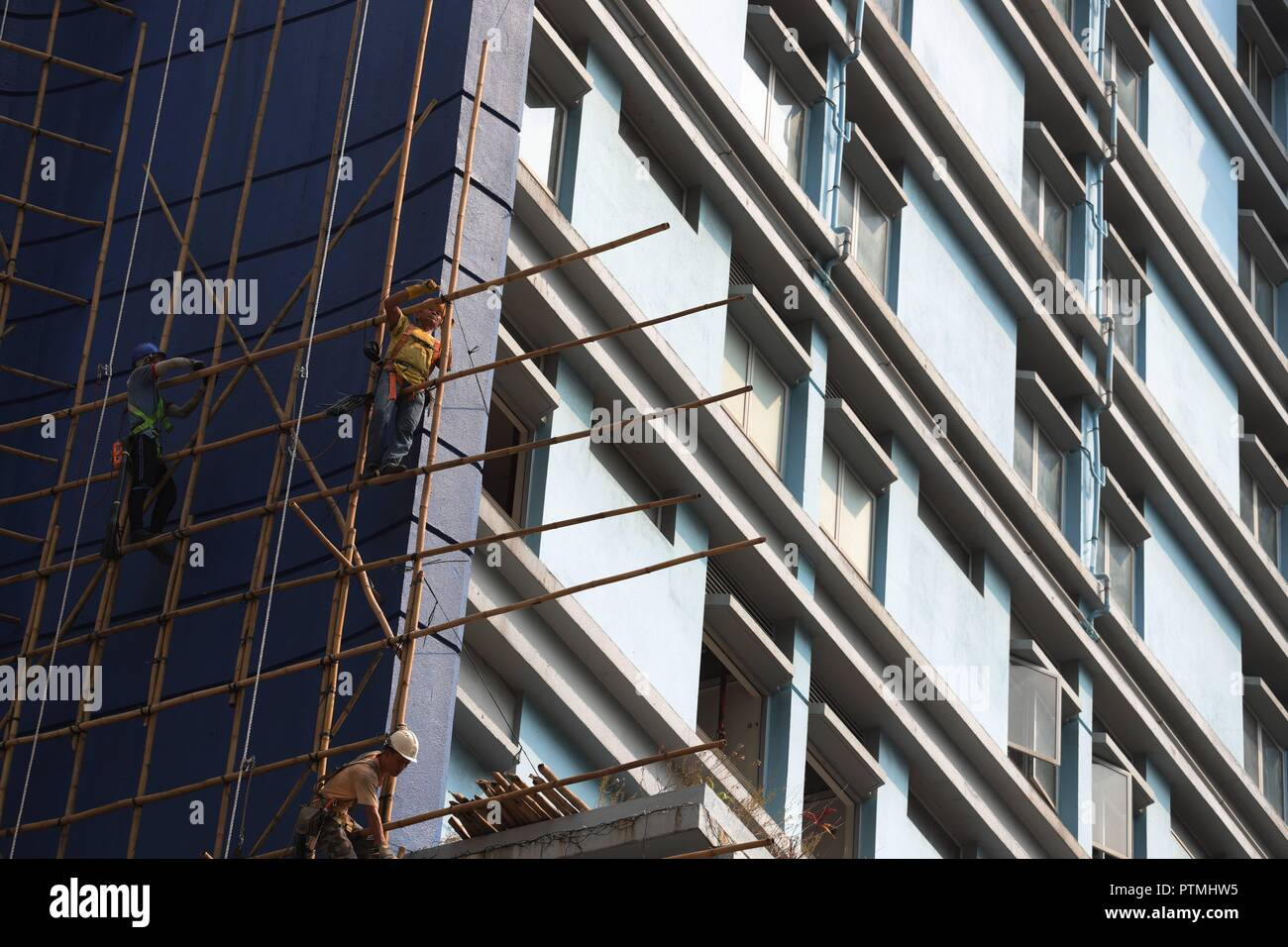 Hong Kong, CHINA. 10th Oct, 2018. Workers perform their duty skillfully on the bamboo scaffoldings outside the hotel awaiting to be demolished. Hong Kong is a place where Chinese traditional art of bamboo scaffoldings are being kept as a classic architectural heritage.Oct-10, 2018 Hong Kong.ZUMA/Liau Chung-ren Credit: Liau Chung-ren/ZUMA Wire/Alamy Live News - Stock Image