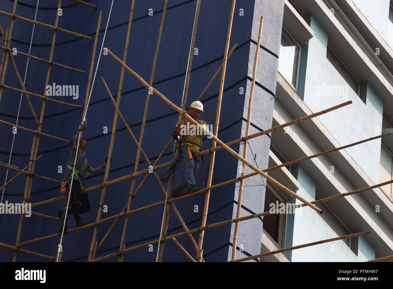 Hong Kong, CHINA. 10th Oct, 2018. A worker carrying a bamboo on the scaffolding outside the hotel awaiting to be demolished. Hong Kong is where Chinese traditional art of bamboo scaffolding is being kept as a classic architectural craft.Oct-10, 2018 Hong Kong.ZUMA/Liau Chung-ren Credit: Liau Chung-ren/ZUMA Wire/Alamy Live News - Stock Image